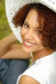 pic of black curly hair  - Happy smiling young woman hanging out in the backyard in a big summer hat - JPG