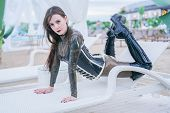 Sexy Young Woman In Erotic Latex Fetish Wear Outdoor On The Beach poster