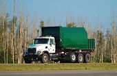 image of waste disposal  - Green colored waste removal dump truck on the road - JPG