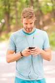 Pairing His Fitness Watch With His Smartphone. Sportsman Using Fitness Tracker For Training Outdoor. poster