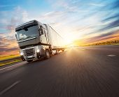 European truck vehicle on motorway with dramatic sunset light. Cargo transportation and supply theme poster