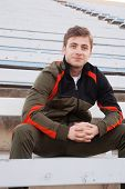 image of bleachers  - handsome male athlete sitting in the bleachers - JPG