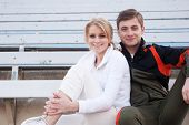 picture of bleachers  - happy male and female athletes sitting in the bleachers - JPG