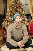 Macho Smile On Furry Carpet At Xmas Tree In Room. Man Sit In Warm Hat, Sweater At Christmas Tree. Ho poster