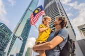 Dad And Son Tourists In Malaysia With The Flag Of Malaysia Near The Skyscrapers. Traveling With Kids poster