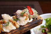Dumplings With Potatoes And Greaves In Sour Cream On A Wooden Board And Salad. Dumplings With Potato poster