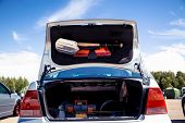 Open The Trunk Of A Silver Car That Stands On The Street. In The Trunk Of A Shovel, Baseball Bat And poster