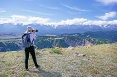 Woman Photographer Taking Photo At Mountain Peak. Hiker Woman With Backpack And Camera Making Photo  poster