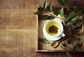 A cup of green tea on wooden tray  with green leaves. Healthy lifestyle. Copy space poster