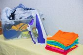 Iron And Baby Clothes. Colored Clothes On An Ironing Board. Bright T-shirts. Ironed And Non-ironed C poster