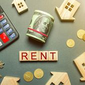 Table With Wooden Houses, Calculator, Coins, Magnifying Glass With The Word Rent. The Concept Of Ren poster
