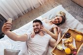 Young Happy Couple Having Breakfast In Luxury Hotel Room Using Smart Phone To Take Selfie Photo. poster