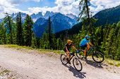 Cycling woman and man riding on bikes in Dolomites mountains andscape. Couple cycling MTB enduro tra poster