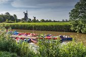 Pedal Boats And Twin Windmills In Greetsiel, North Sea, East Frisia, Germany poster