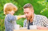 Dad And Boy Eat And Feed Each Other Outdoors. Ways To Develop Healthy Eating Habits. Feed Your Baby. poster