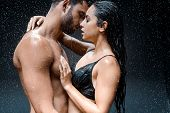 Attractive Woman Hugging Shirtless And Wet Man Under Raindrops On Black poster