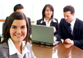 picture of latin people  - business woman in an office environment with people working behind her - JPG
