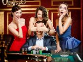 stock photo of roulette table  - Girls cover the eyes of the gambler playing roulette at the casino - JPG