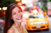 Happy New York City girl. Woman smiling laughing joyful on Manhattan with yellow taxi cab in backgro