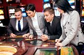 Excited people looking at spinning roulette in casino