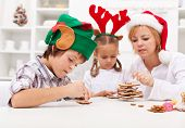 Kids decorating gingerbread cookies together with their mother