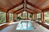 stock photo of swimming pool family  - Swimming pool in luxury home with wood ceiling - JPG