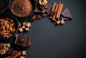image of mixed nut  - Black and milk chocolate cocoa powder nuts sweets spices and brown sugar on a black background food concept - JPG