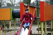 picture of nursery school child  - child playing on red and orange slide - JPG