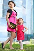 stock photo of bolero  - Beautiful girl with tablet pc and little girl in red stand near blue skyscrapers - JPG