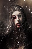 image of spiderwebs  - Female face of dark horror lurking in the shadows of darkness beneath the spin of spider webs - JPG