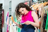 stock photo of boutique  - Young woman looking at expensive price tag while fashion shopping in boutique or store - JPG