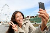 Asian tourist in London taking self-portrait photo smiling happy showing victory v hand sign with Lo