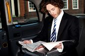 picture of cabs  - Handsome young businessman reading newspaper inside taxi cab - JPG