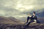 picture of spyglass  - elegant man with cylinder looks through a telescope sitting on a chair in the mountain - JPG