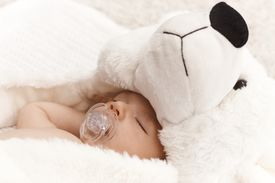 picture of teats  - Closeup photo of beautiful baby with dummy and big bear hat - JPG
