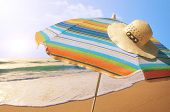 Detail of colorful sunshade and straw hat in the beach on a sunny summer day