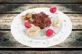meat beef bourguignon in wine with artichoke and marinated vegetables on white plate isolated over w