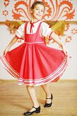 Beautiful girl in red folk costume dances near wall with pattern