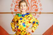 Beautiful girl dressed as jester poses and smiles near wall with pattern