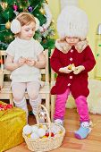 Two little girls sit on wooden chairs in room with decorated christmas tree and skin tangerin