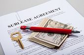 stock photo of rental agreement  - Sublease agreement with dollar notes golden key and pen