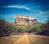 Vintage retro hipster style travel image of famous ancient Sigiriya rock with grunge texture overlai