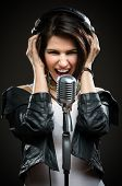 Half-length portrait of female rock musician with microphone and earphones. Concept of rock music an