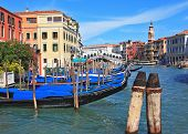 The famous Grand Canal in Venice. Graceful black gondolas wait for passengers on the mooring at the