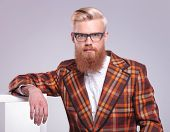 stock photo of long beard  - fashion man with long red beard and glasses resting in studio looking at the camera - JPG