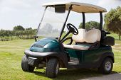 pic of caddy  - Empty electric golf cart parked on a fairway at a golf club in the hot summer sunshine - JPG