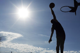 stock photo of slam  - Silhouette of a male basketball player in mid air about to slam dunk the ball with the sun creating a flare effect - JPG