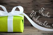 stock photo of weihnachten  - Green Christmas Gift with the German Words Frohe Weihnachten which means Merry Christmas