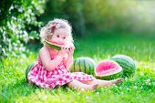 stock photo of healthy eating girl  - Funny little girl adorable toddler with curly hair wearing a red dress eating watermelon healthy fruit snack playing in a sunny garden on a hot summer day - JPG
