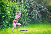 stock photo of fountain grass  - Funny laughing little girl in a colorful swimming suit running though garden sprinkler playing with water splashes having fun in the backyard on a sunny hot summer vacation day - JPG